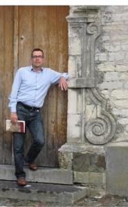 Ward Caes met boek Max Deauville aan kerk Wakkerzeel (foto Conny Justé)
